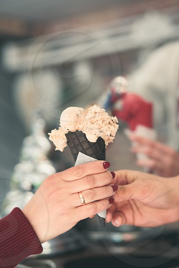 Woman buying couple scoops of  ice cream in a candy shop by a street. Woman putting a scoops of ice cream to a cones photo