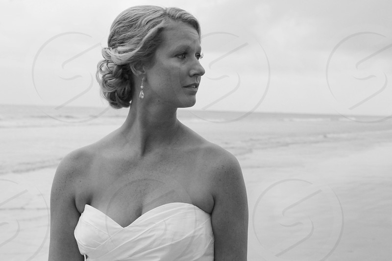 bride wearing a white strapless gown looking to the side on the beach photo