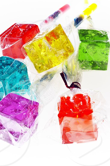bounch of colorfull translucent dice shaped lollipops backlit on white background photo