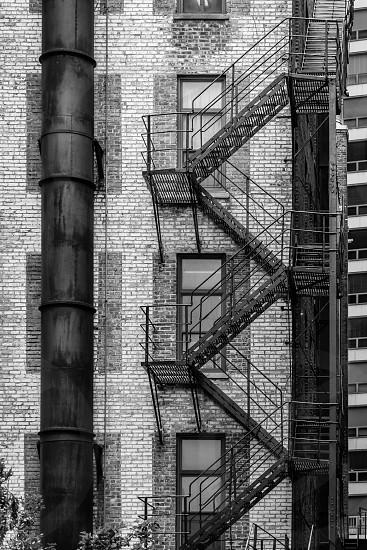 city building urban fire escape ladder metal brick black white B&W photo