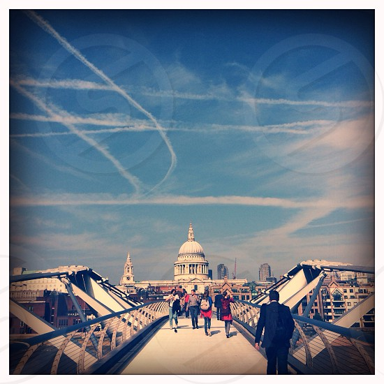 People walking over Millennium Bridge London England with a view to Saint Paul's Cathedral in the distance.  photo