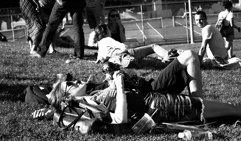 Couple with a dog at the park smoking a cigarette in black and white.  photo