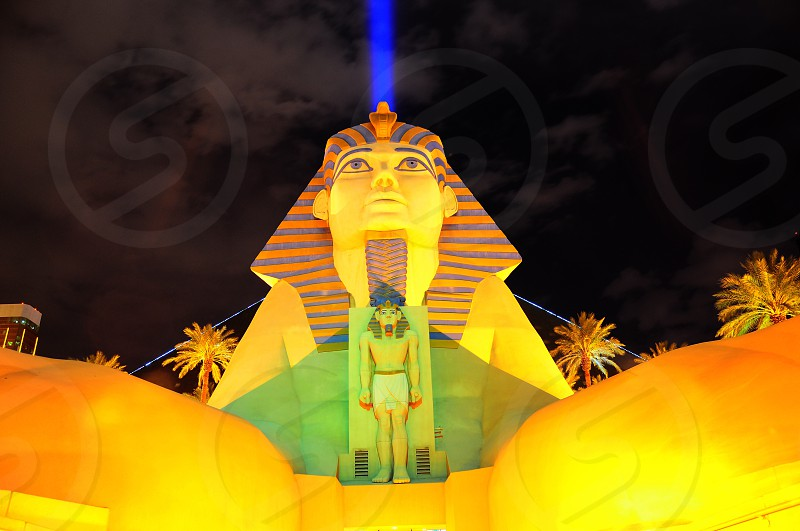 sphinx with yellow light under gray clouds during nighttime photo