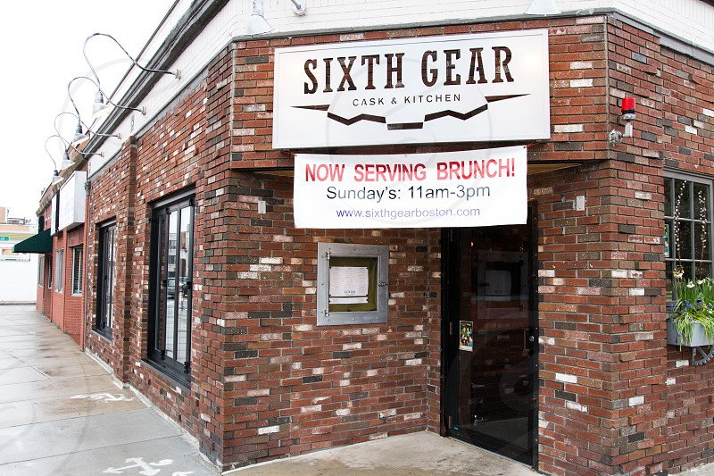 sixth gear store sign board on brown wall bicks photo