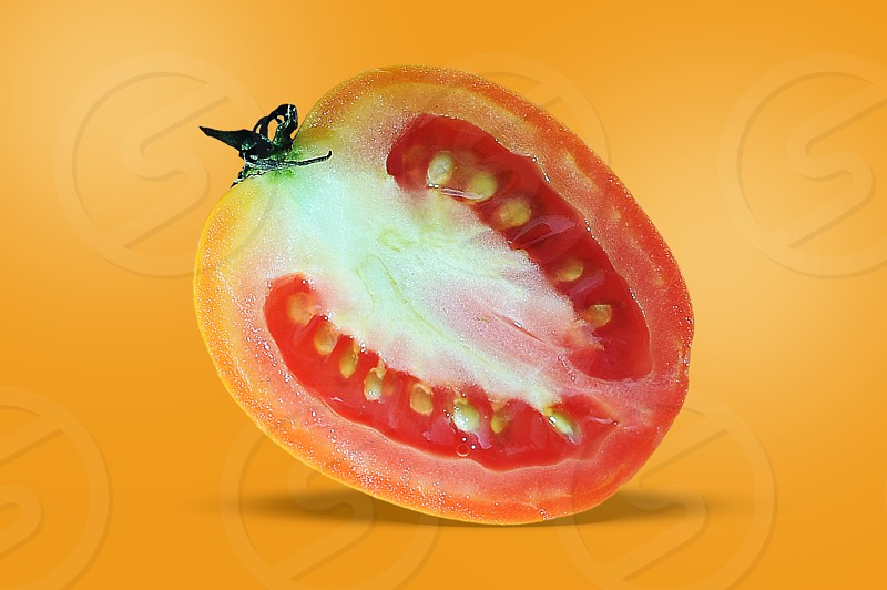 Tomato. a half of tomato slice tomato fly tomato isolated on orange background photo