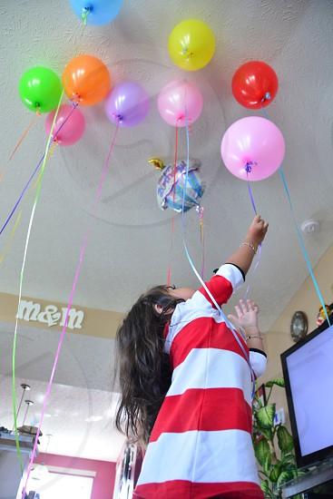 girl reaching for pink balloon photo