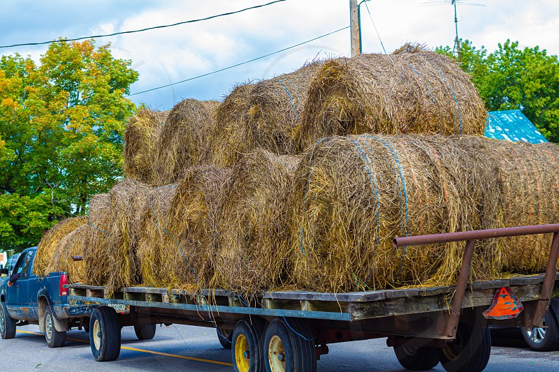 A pickup truck drives by towing a trailer with several baled of hay. photo