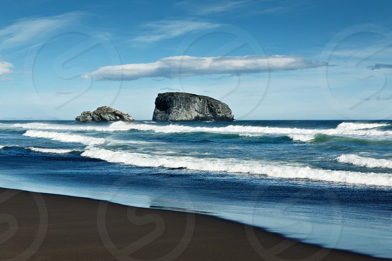 Nature of Kamchatka: beautiful view of the Pacific Ocean the island in the ocean and beach with black volcanic sand on a sunny day. Kamchatka Peninsula Far East Russia. photo