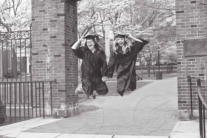 two girls in black cap and gown jumping up and down holding hands photo