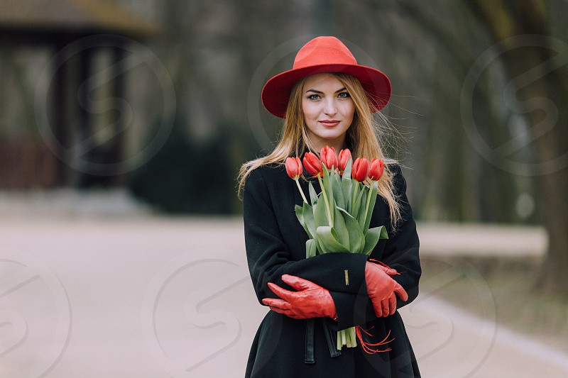 smiling blonde woman wearing a red hat black coat with red gloves holding a bouquet of red tulips on a park path photo