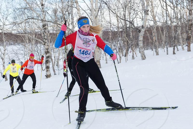 PETROPAVLOVSK KAMCHATKA PENINSULA RUSSIA - FEBRUARY 10 2018: Pretty young sportswoman running on skis in winter forest. All-Russia mass ski race - Ski Track of Russia. photo