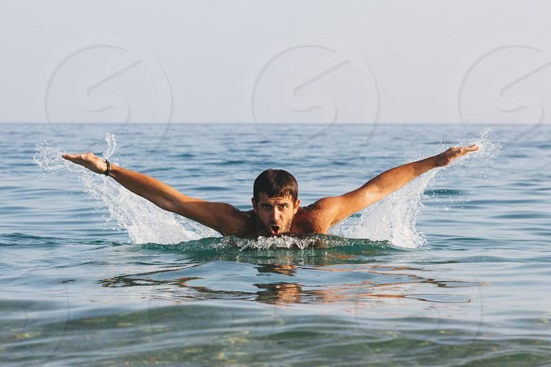 Young handsome man swimming butterfly style in the sea photo