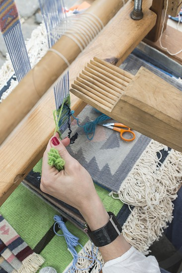 Young woman weaving loom. Small carpet photo