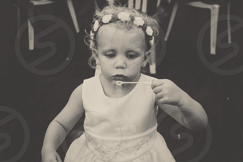 toddler blowing bubbles in white flower halo and tank dress photo