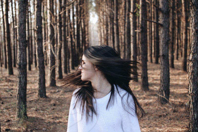 woman whipping her hair in the middle of the forest during daytime photo