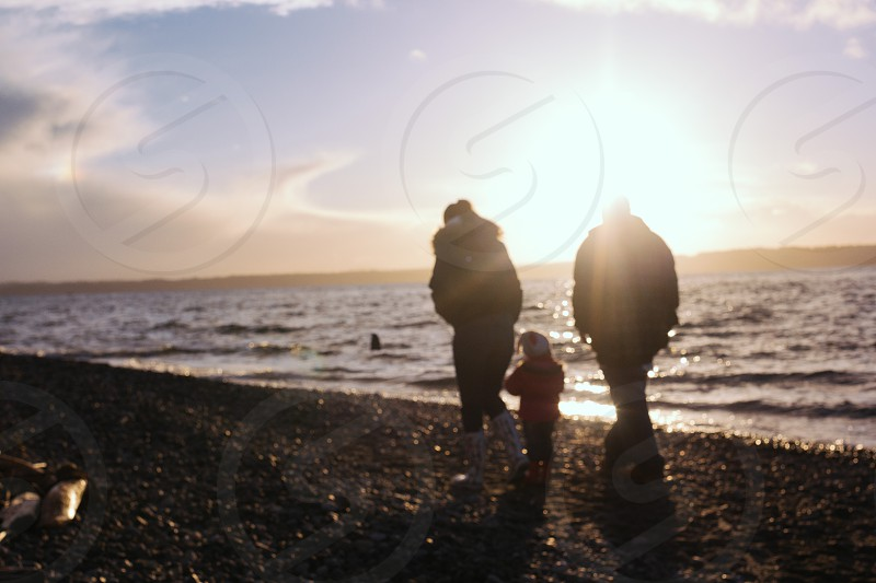 mother father and child walking on seashore during sunset photo