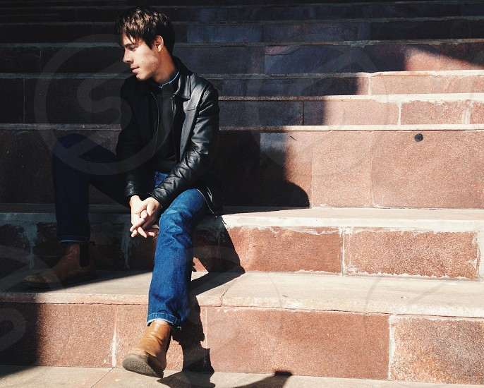 man wearing black leather jacket sitting on brown staircase photo