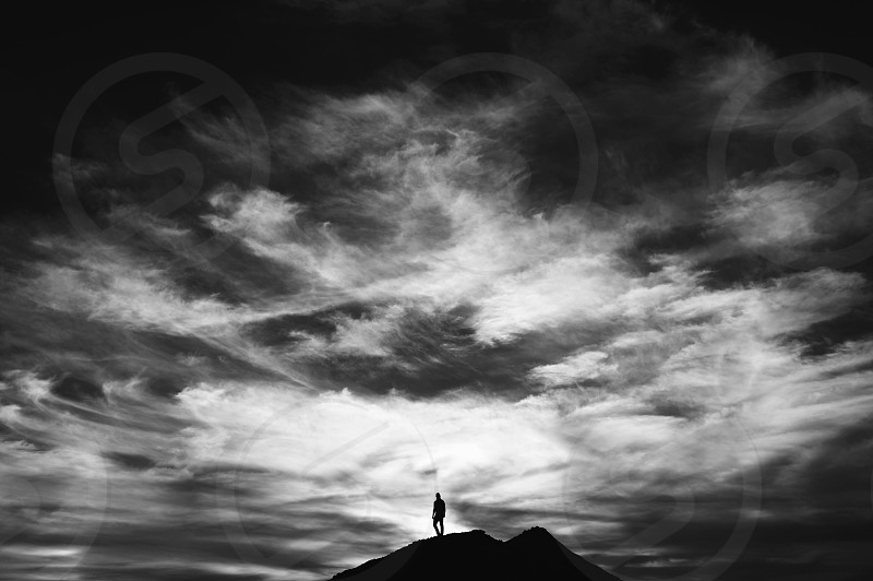 person's silhouette on a mountain photo