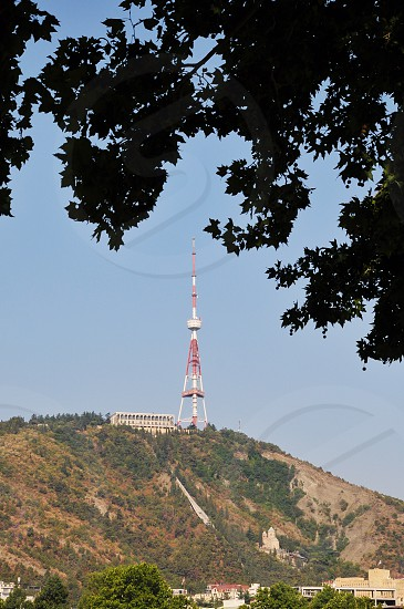 red and white satellite tower on mountain top under blue clear sky photo