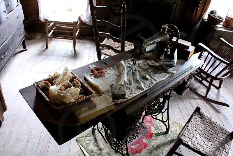 Old sewing machine and notions in room of 1880s cottage photo