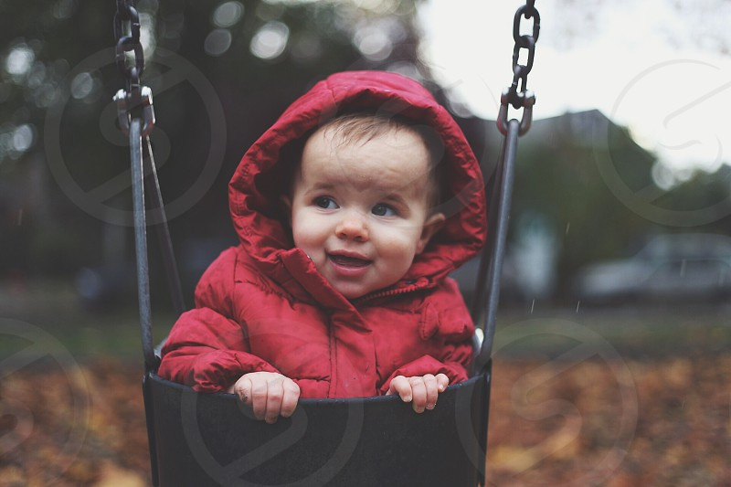Bundled baby on the swing.  photo