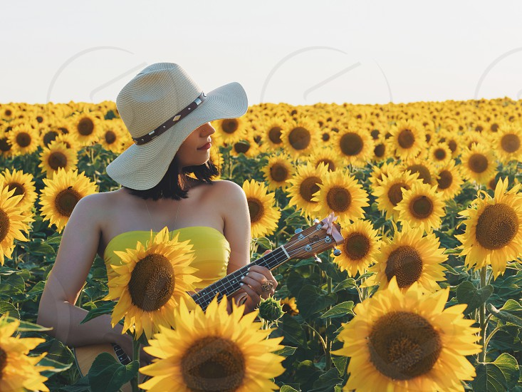 Happy woman in sunflower field. Summer girl in flower field cheerful and joyful.Caucasian young lady in cowboy hat dancing smiling elated and serene with arms raised up. photo