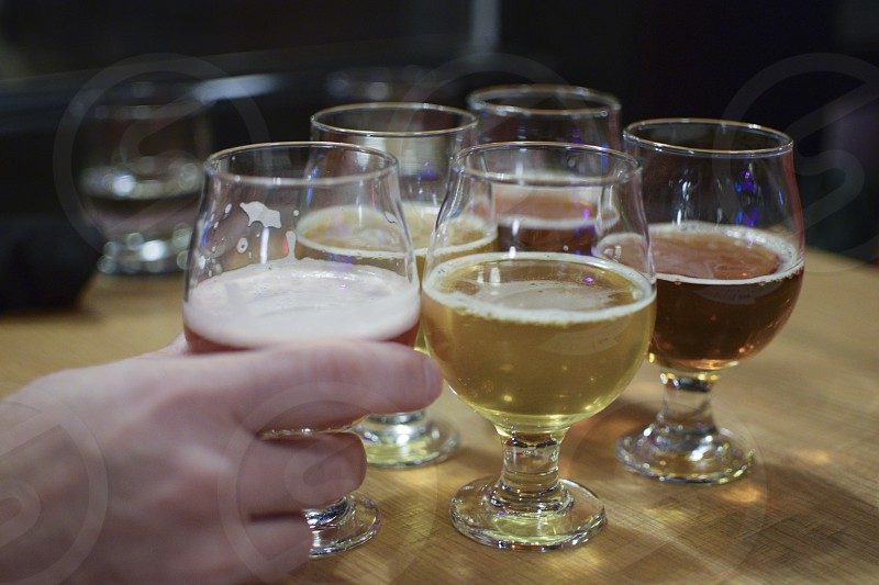 A flight of beer set out on a table in a restaurant with a man's hand reaching for one of the glasses. photo