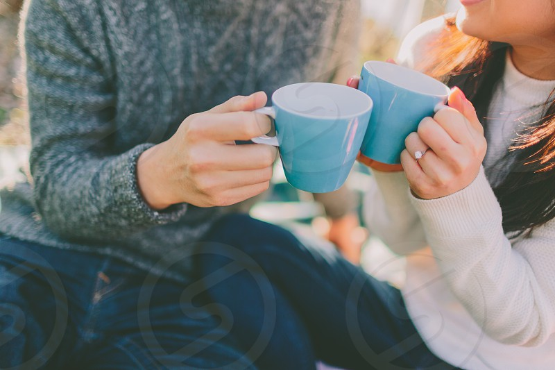 A couple having hot drinks together in the sunshine on a cold day.  photo