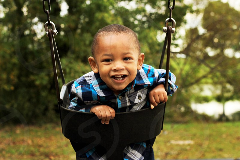 boy in blue white and black plaid button up sport shirt on black swing during daytime photo
