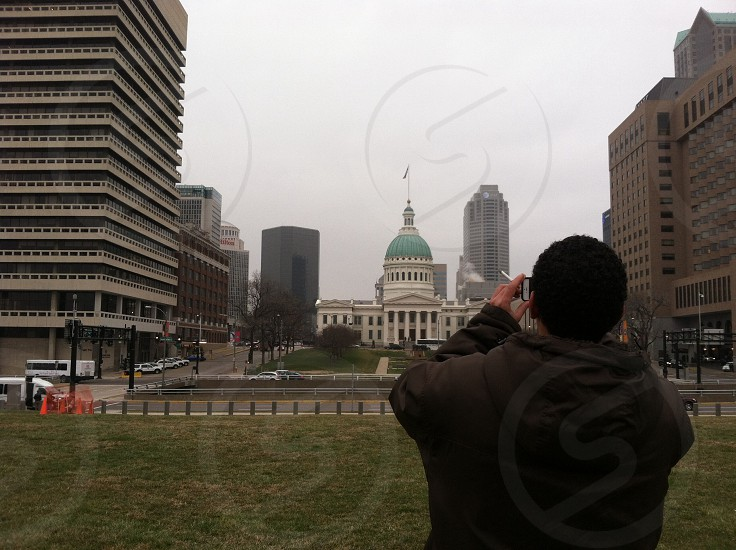 man in brown hoodie taking a photo of the green and white dome infrastracture photo