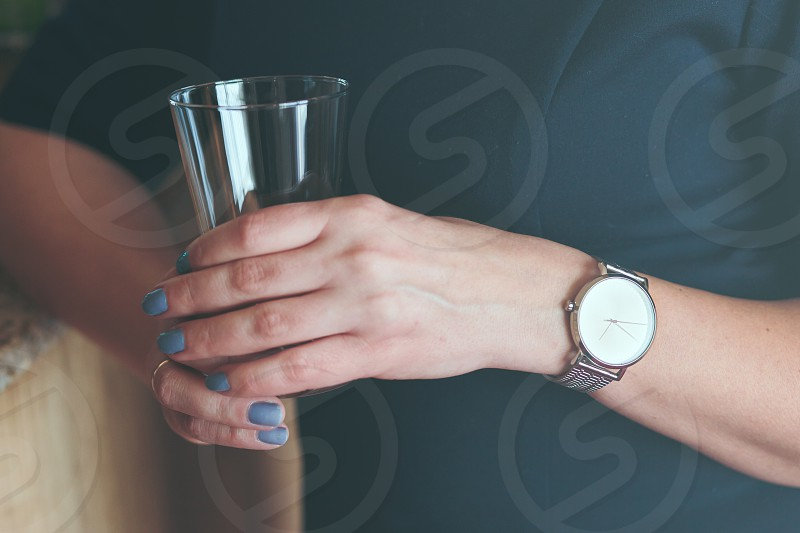Elegant woman wearing silver wristwatch and blue dress holding glass of water photo