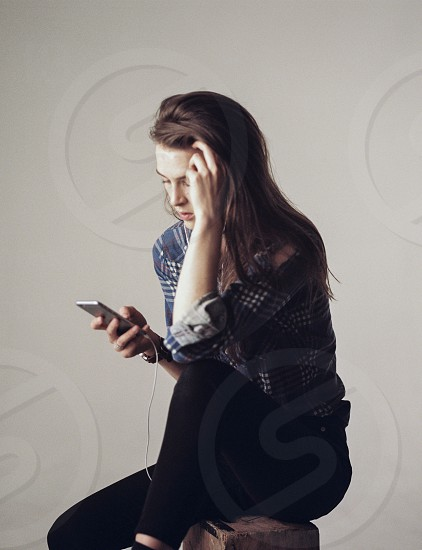 woman in gray and white plaid formal shirt and black skinny pants using silver iphone 6 sitting on brown wooden box photo