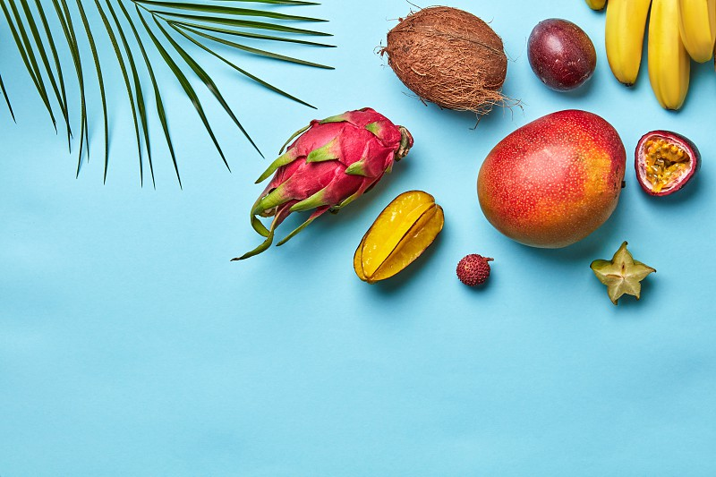 Corner frame of a green palm branch and a variety of tropical fruits on a blue background with space for text. Flat lay photo