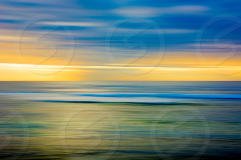 artsy colorful blurr water yellow blue green waves sky clouds ocean photo