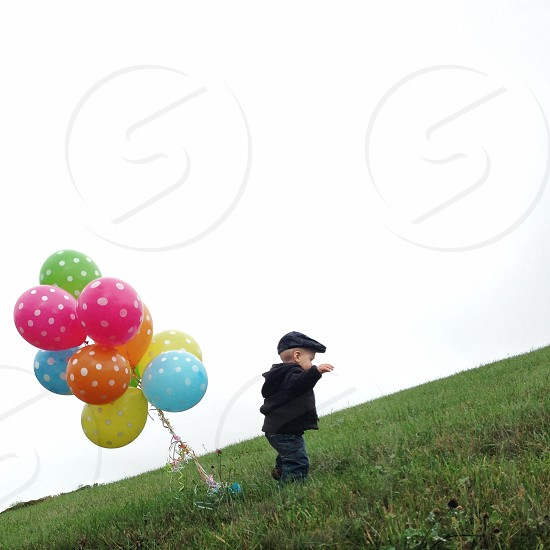 small boy walking away from colorful balloons photo