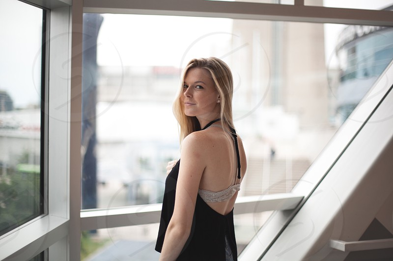 woman in black halter top near the glass window during daytime photo