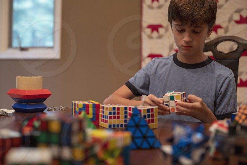 Boy tween plays with puzzle cube photo