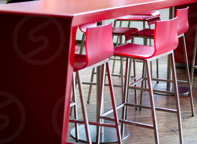 Red tall bar chairs in a row with one of them pulled back. photo