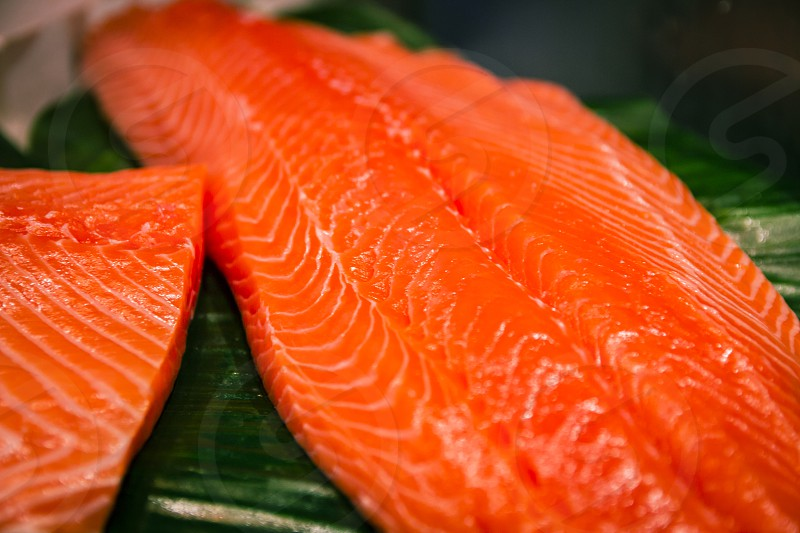 Sliced salmon laid on a green surface. photo