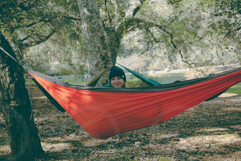 woman in black knit cap smiling and lying on red and black hammock photo