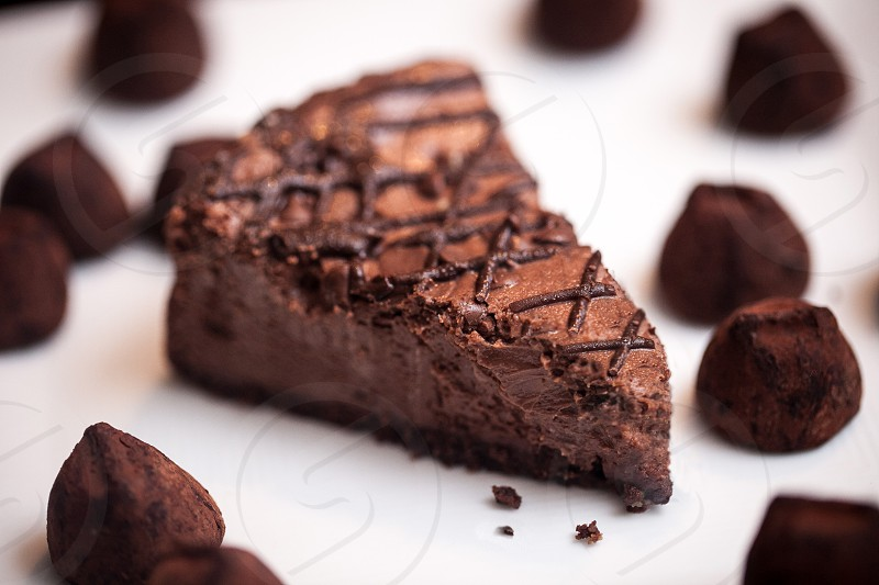 A slice of chocolate cheesecake with cookie crumb crust surrounded by dark chocolate truffles. photo