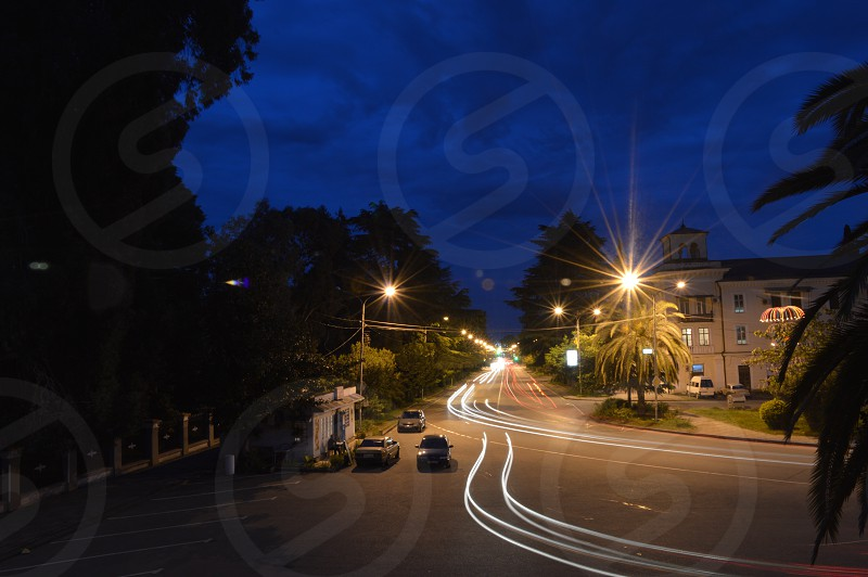 time lapse photography of vehicle's trail lights on a road during nighttie photo