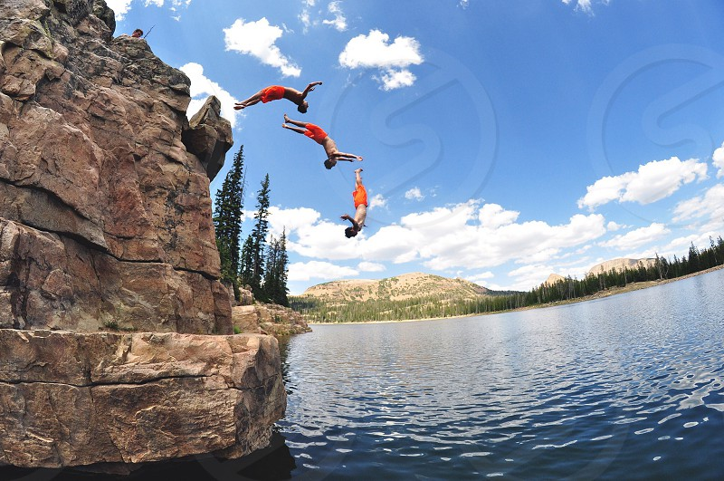 person diving of rock in lake 3 different times photo