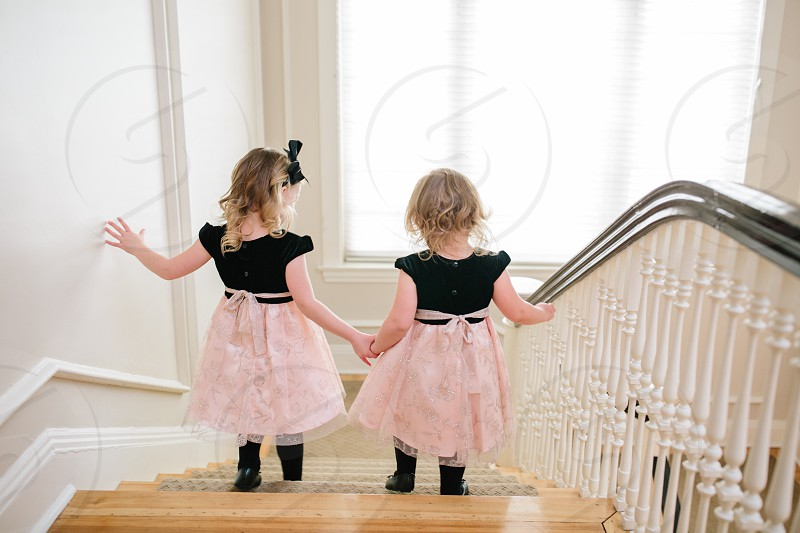 Two little girls holding hands going down the stairs photo