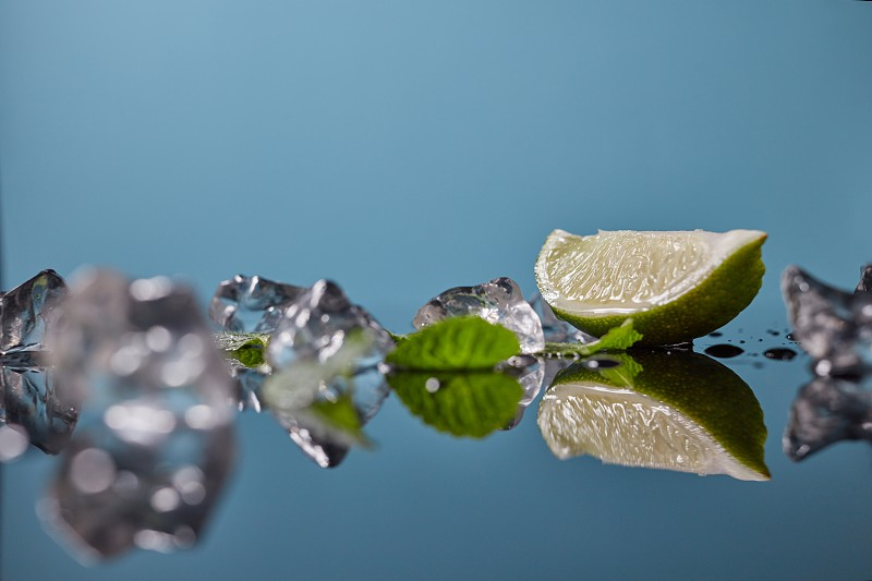 A slice of lime a lemon with green mint leaves is reflected on the mirror surface with crushed transparent ice cubes with a soft focus photo