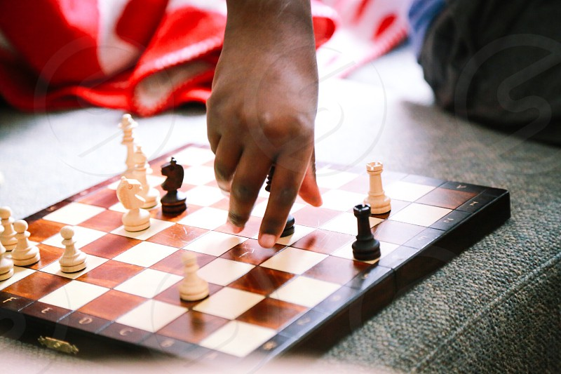 Game home sofa kid playing chess chess player hand closeup  photo