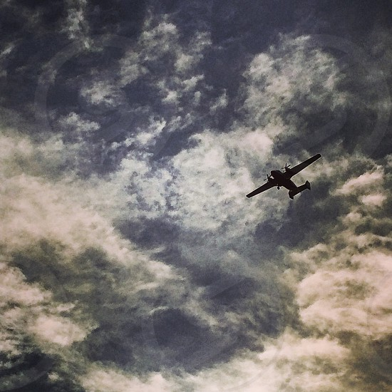 low angle photography of airplane arriving under white clouds during daytime photo