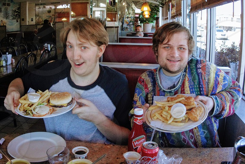 Two best friends eating burgers photo