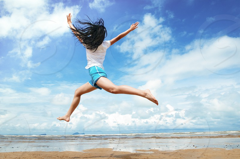 fitness female workout beach exercise leaping up in air freedom healthy lifestyle wellness wellbeing people one person young adult young woman day blue sky horizontal landscape scenery photo