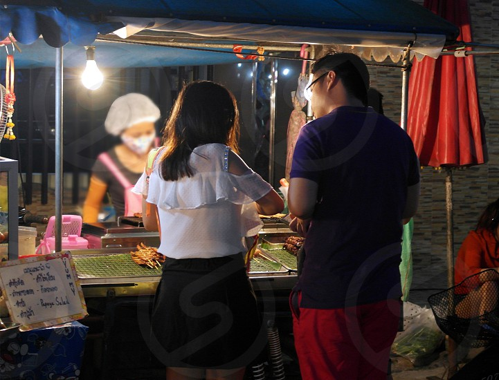 man in blue polo shirt beside woman in white blouse eating on street food during nighttime photo